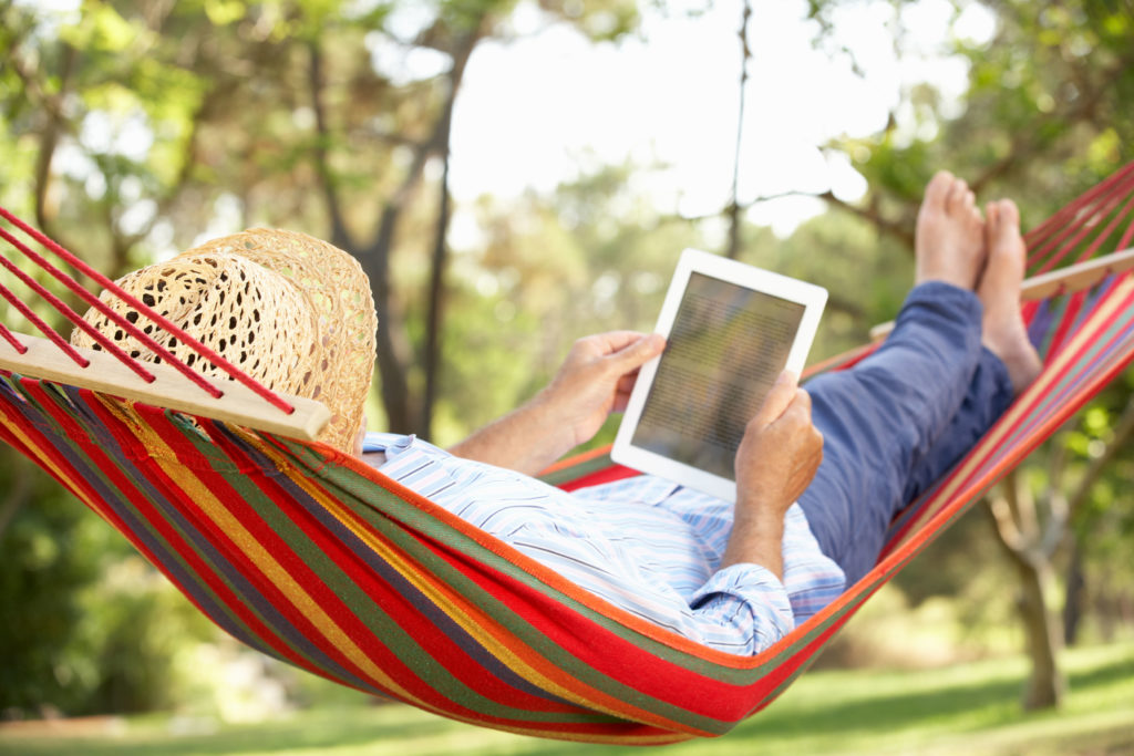 Man laying in hammock reading on tablet