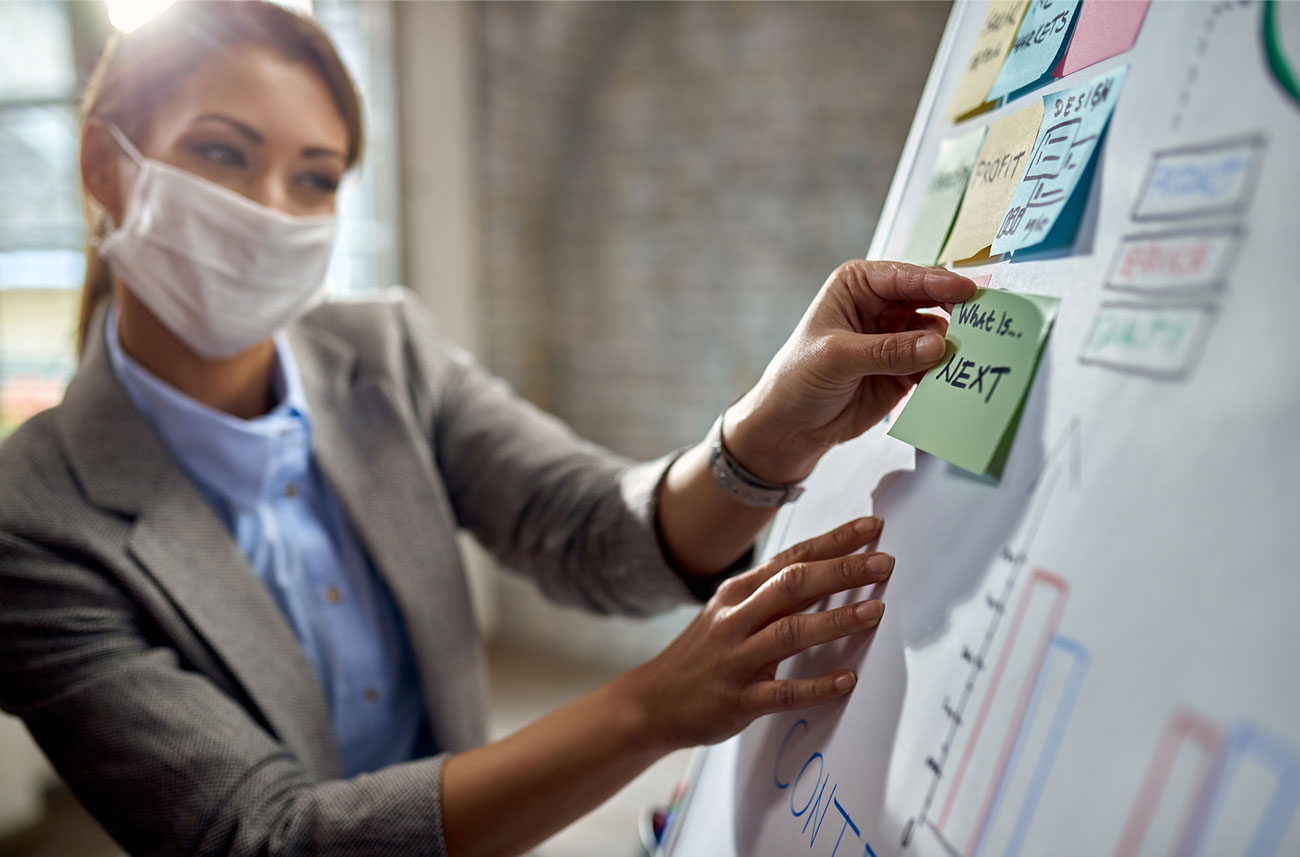 woman wearing face mask in office working on a white board with sticky-notes