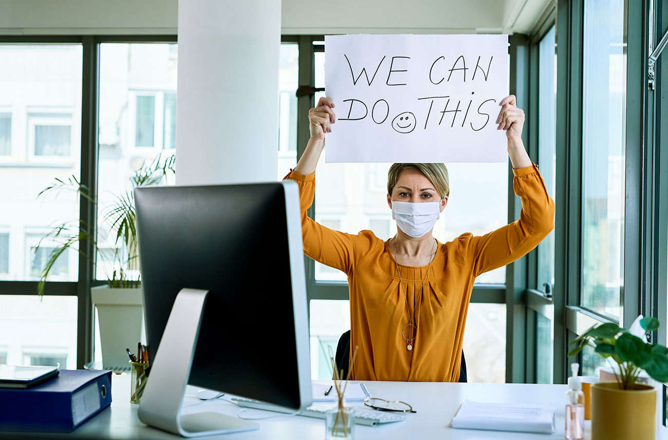 woman working holding up sign with encouraging message