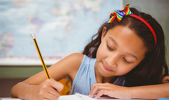 Girl writing in notebook with pencil at school