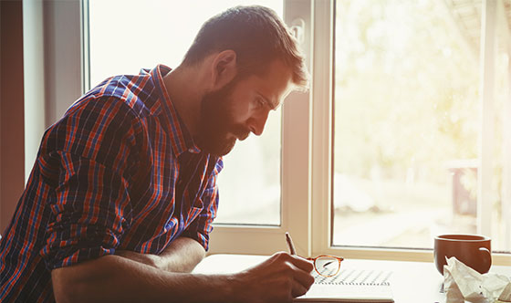 Man writing in notebook at home