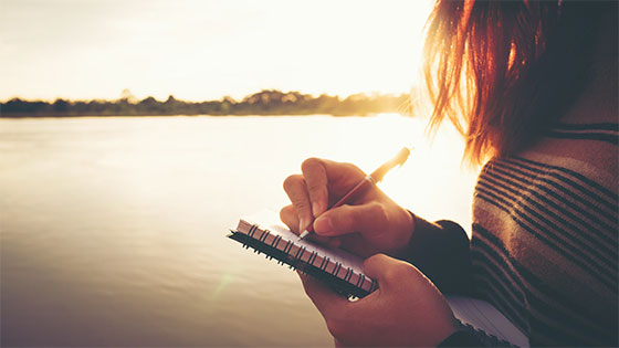 Woman writing in spiral bound notebook outside during sunset