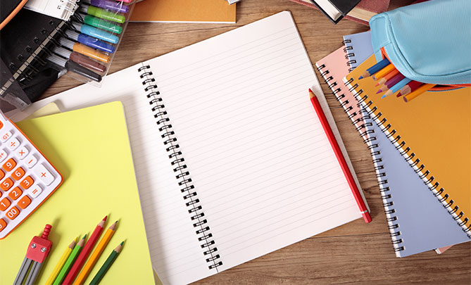 School supplies on desk notebooks and colored pencils