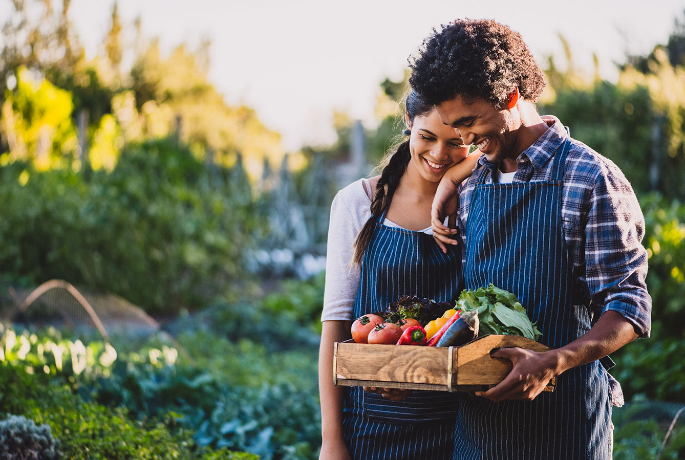 Couple in home garden with vegetable harvest