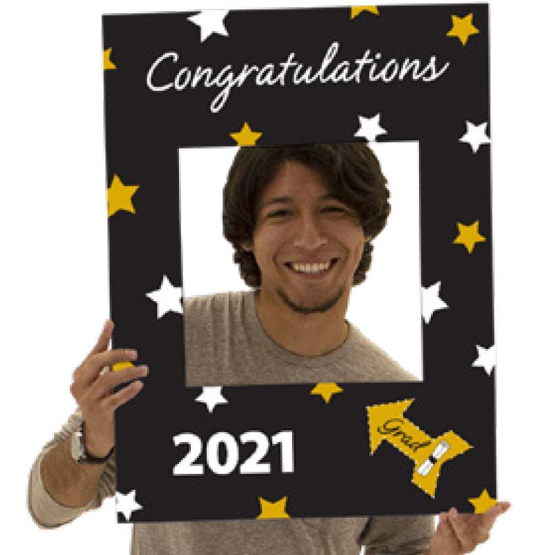 Young man using graduation selfie frame